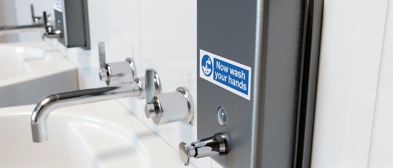 Dávkovač mýdla v nemocniční koupelně s nalepeným odolným štítkem Brother P-touch TZe
