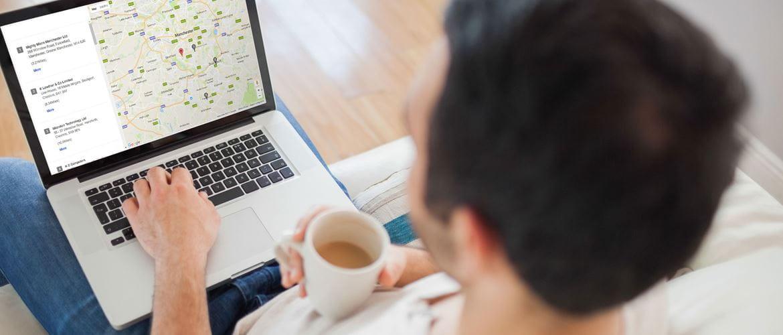 Мъж държи чаша с кафе и разглежда карта с контакти на оторизирани Brother партньори на лаптоп.