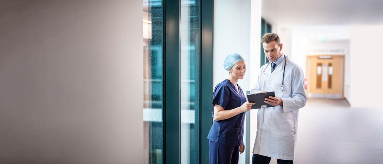 Doktor v bílém plášti se stetoskopem a lékařka v modrém plášti v chodbě nemocnice