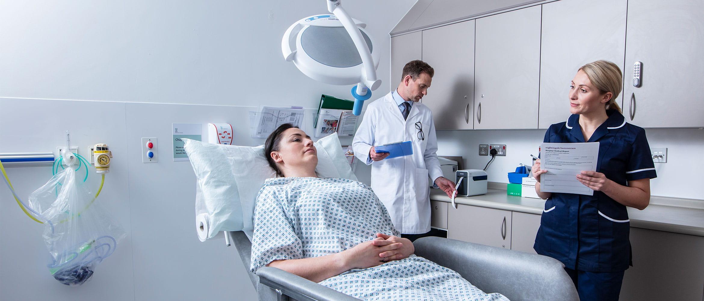 Pacientka leži na postelji, ob njej medicinska sestra z obrazcem, v ozadju zdravnik v beli uniformi