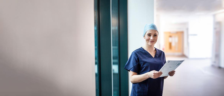 Žena v chirurgickom odeve držiaca modrú zložku, v chodbe s dverami v pozadí