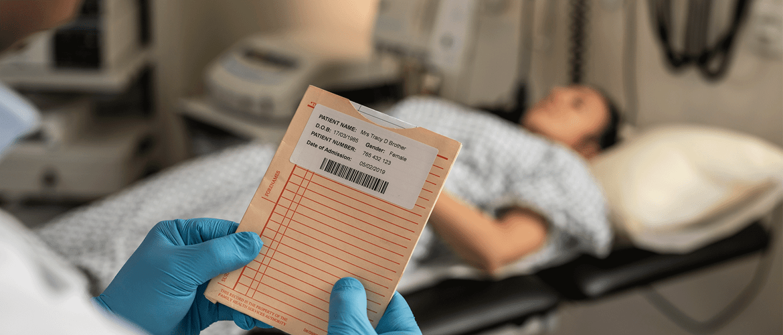 Pacijentica leži u bolničkom krevetu, a kraj nje liječnik drži kartoteku s naljepnicom