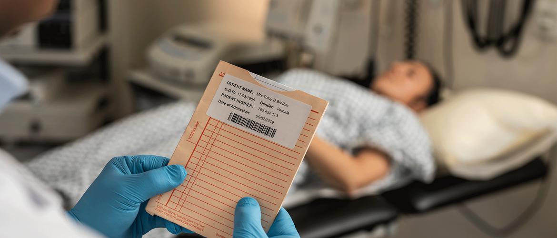 Pacientka ležiaca na nemocničnej posteli, doktor kontrolujúci záznamy