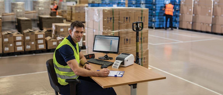 Moški sedi za mizo v skladišču in nosi rumen opozorilni jopič, monitor, tipkovnica, tiskalnik nalepk Brother TD, škatla, voziček s paletami
