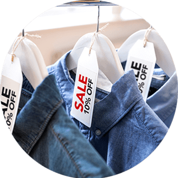 Red and black sale labels on hangers holding denim shirts