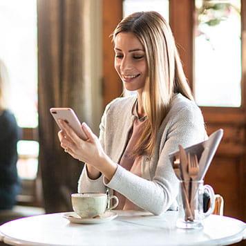 žena v kaviarni používajúca aplikáciu pre tvorbu štítkov na smartfone