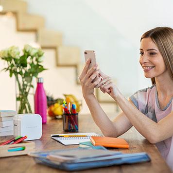 Ženska na telefonu oblikuje nalepke za P-touch CUBE prek povezave Bluetooth, s stopnicami v ozadju