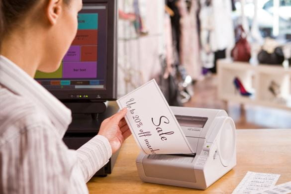 Shop worker printing a large sale sign on a continuous label and TD-4000 series label printer