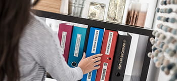 Picture of woman putting a labelled file on a bookcase