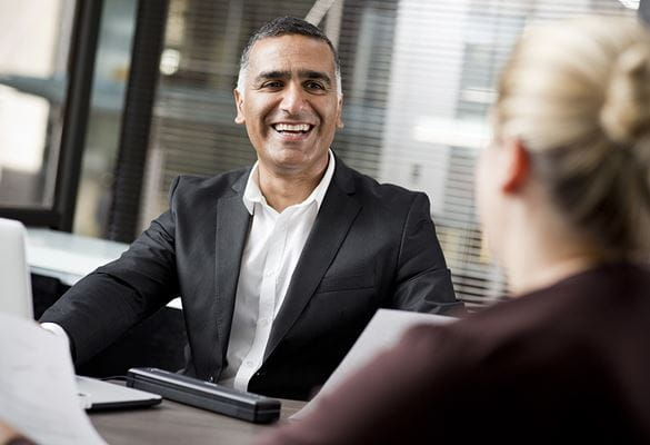 Business man laughing while sat at table with business woman