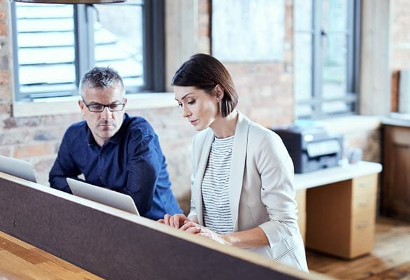 Business man and woman looking at computer screen in office