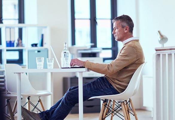 En mann jobber på datamaskinen på et kontor