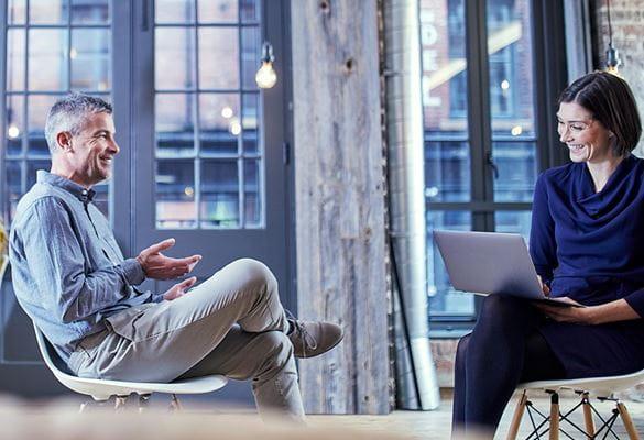 En mann og en kvinne sitter å snakker sammen på et kontor