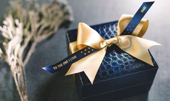 confezione regalo blu con nastro blu e scritta oro con fiocco oro