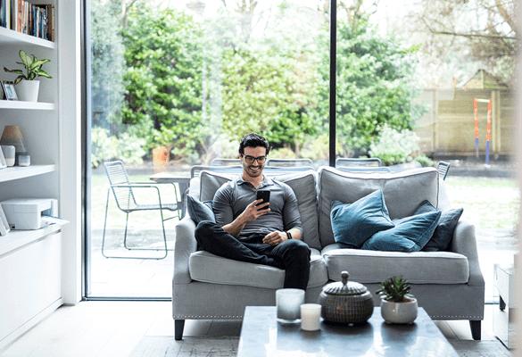 Mann sitter i sofaen hjemme og bruker mobiltelefon