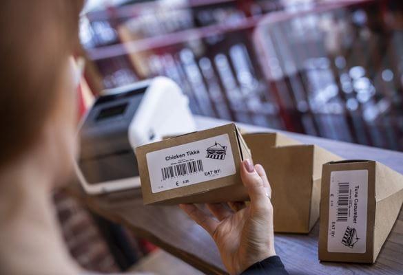 Egy nő ellenőrzi a Brother címkézőgép nyomtatott élelmiszer-címkéit, amelyeket egy élelmiszercsemege vagy pékség boltban előrecsomagolt szendvicsekre ragasztottak. A címkék vonalkódot, címet, képet, árat és dátum szerinti felhasználást tartalmaznak.