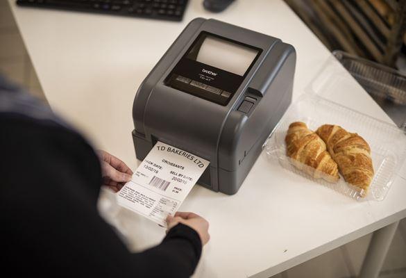 Prim plan cu o imprimantă de etichete Brother imprimând o etichetă pentru alimente, pentru un pachet de cornuri în back office-ul unui magazin de delicatese, al unei brutării sau al unei cafenele