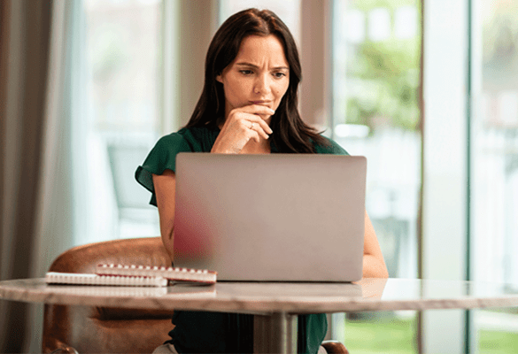 Woman sat at a home office desk looking at a laptop screen and pondering