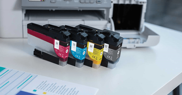 zoomed in image of brother colour printer, with colour cartridges next to it