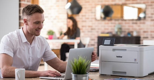 Man in white shirt on his laptop printing from his home printer