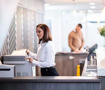 Female wearing white shirt scanning document in reception, man in brown jumper, flowers
