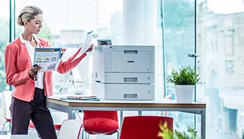 Woman stood picking document from printer, table, plant, red chairs, large windows