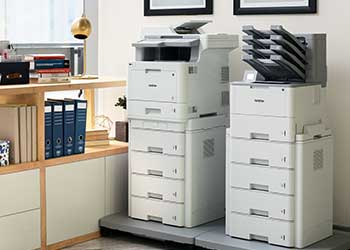 Two floor standing printers side by side against a wall, cabinets, folders, picture frames