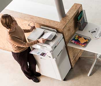 Female stood at printer scanning a document, table, documents
