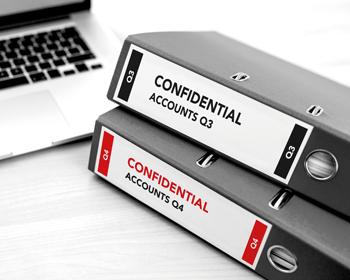 To sorte permer med etiketter hvor det står konfidensiell med sort og rød tekst