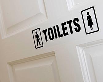 Door sign indicating toilets printed on Brother DK film label using QL label printer