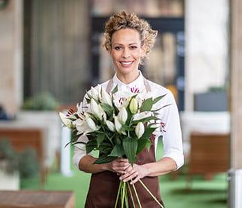 Žena kovrčave kose skupljene otraga, smeđe pregače, drži veliki buket cvijeća
