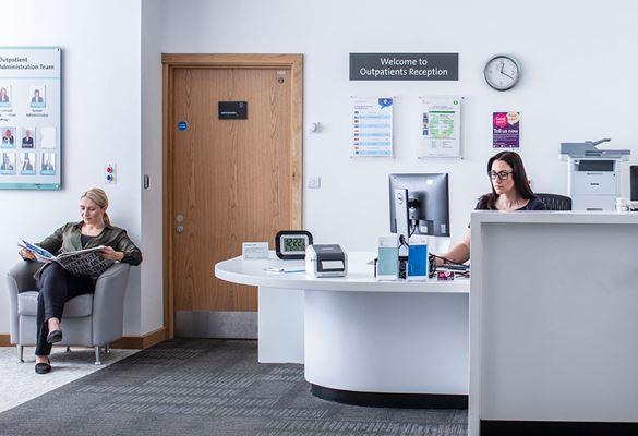 Női recepciós ültaz asztalnál egy számítógép előtt, a női beteg újságot olvas a háttérben