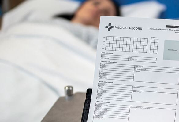 Pacientka leži v postelji, dokumenti skener ADS-3600W Brother skenira jene dokumente