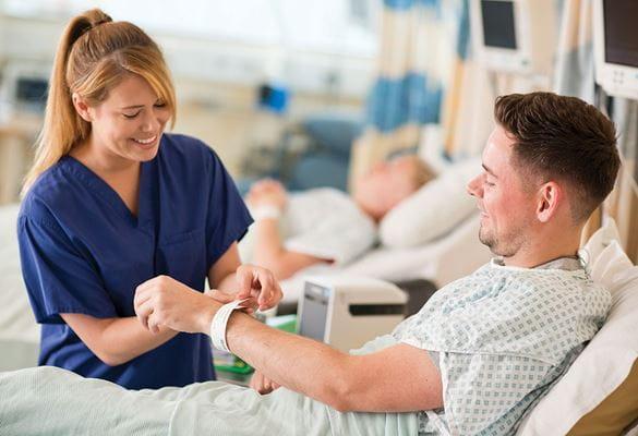 Pielęgniarka w niebieskim fartuchu nakładająca opaskę identyfikacyjną na nadgarstek pacjenta siedzącego na łóżku