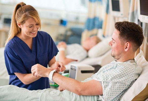 Az ápolónő kék, egészségügyi ruhában az azonosító karkötőt helyezi fel a beteg csuklójára