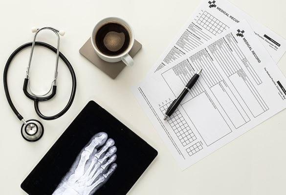 Medicinski obrazci, pisalo, skodelica kave na podstavku, stetoskop, rentgenski posnetek stopala stopala na beli mizi