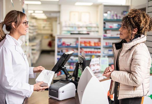Farmacevtka z očali na prodajnem okencu streže žensko s kodrastimi lasmi, oblečeno v plašč