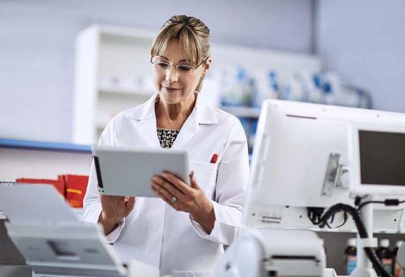 Farmaceutkinja u bijeloj uniformi koristi tablet
