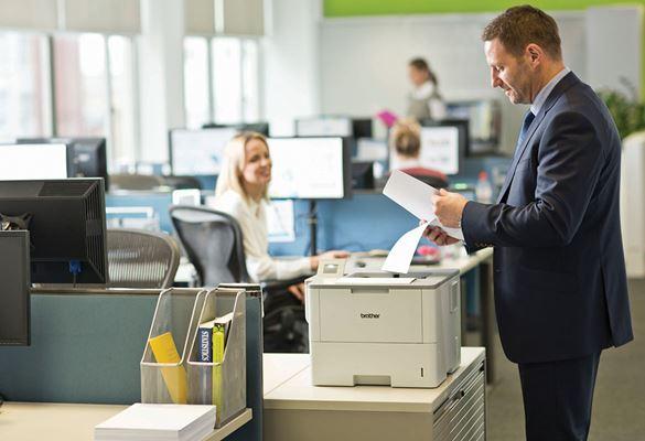 Öltönyt viselő férfi áll a nyomtató mellett és papírt tart a kezében, a háttérben monitorok, hölgy, irodai kép, asztal