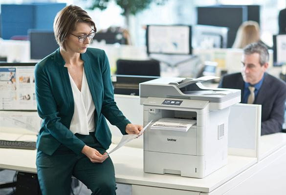 Woman wearing glasses, green suit sat on table next to Brother MFC-L6900DW printer, man wearing suite, monitors, desks