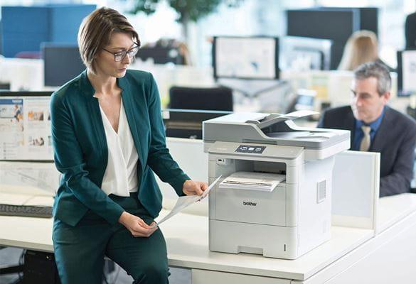 Ženska z očali, v zelenem hlačnem kostimu sedi na mizi poleg večfunkcijske naprave Brother MFC-L6900DW, moški v obleki, monitorji in pisalne mize