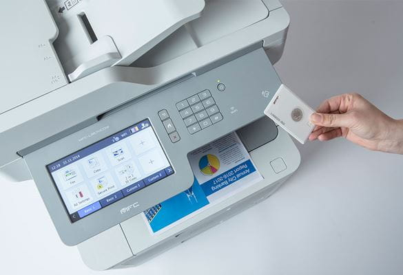 Person's hand holding card against Brother multifunction printer with large screen