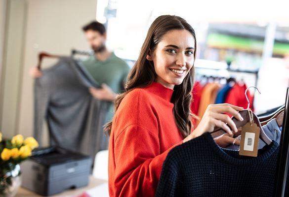 Žena s dlouhými hnědými vlasy v oranžovém svetru drží černou blůzu na věšáku, muž v zeleném tričku si prohlíží šedé sako