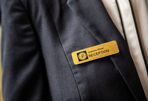 Gold glittery staff identification badge on a grey suit jacket