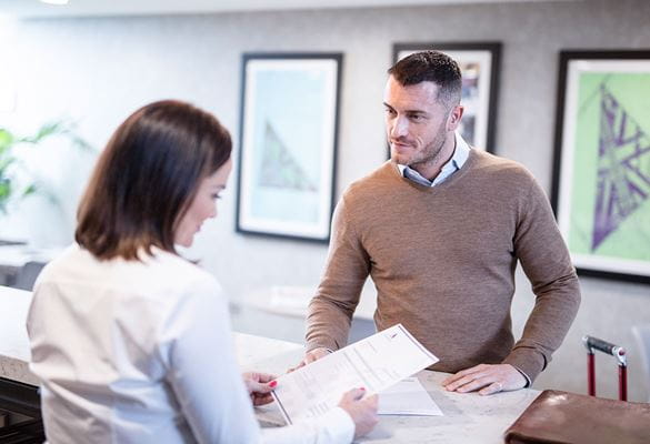 Woman with brown hair wearing white shirt holding paper behind customer services desk, man wearing brown jumper, white shirt
