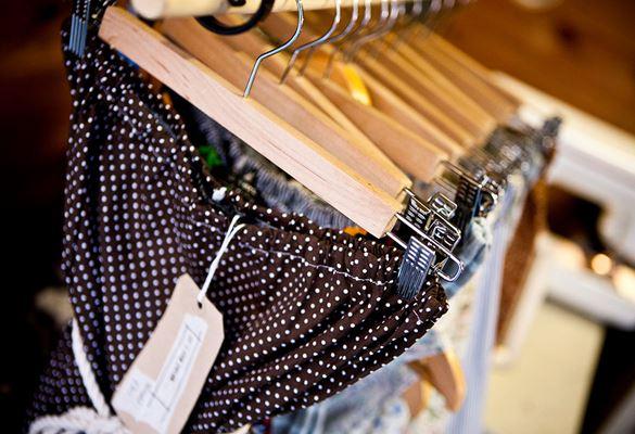Modré bodkované nohavice s cenovkou a topy zavesené na drevených vešiakoch