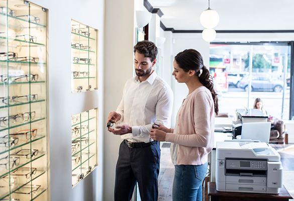 Angajat în alb ținând ochelari alături de clientă,  imprimantă Brother