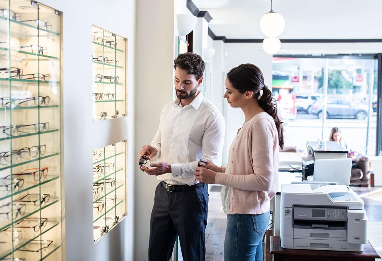 Muškarac u bijeloj košulji koji drži naočale, žena duge smeđe kose vezane u rep, u ružičastom džemperu, trapericama, Brother pisač, naočale, laptop