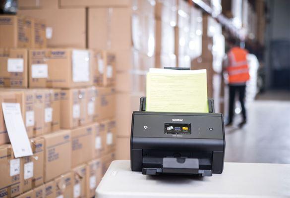 Brother ADS-3600W z odpremnicami v skladišču, skladiščnik v oranžnem opozorilnem jopiču v ozadju, škatle, miza