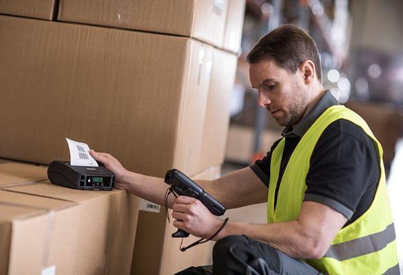 Muž v reflexnej veste držiaci ručný skener, tlačiareň štítkov na krabici v sklade